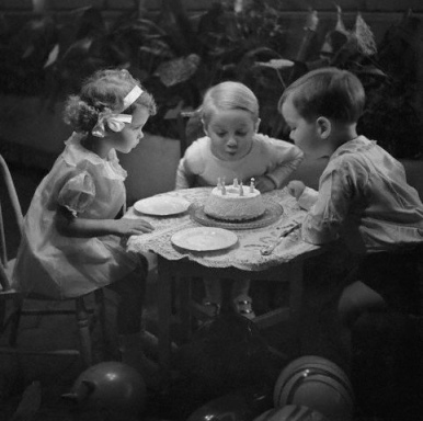 little kids blowing out birthday cake by Foxtongue at flickr